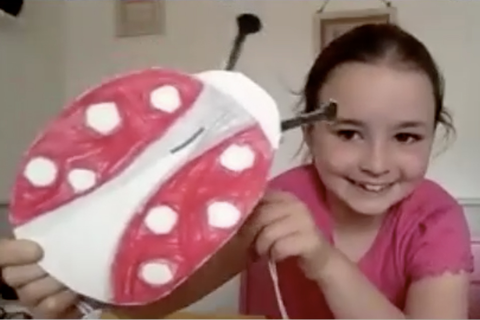 Girl holding ladybird using card hinges - Kids Own Reinvention project