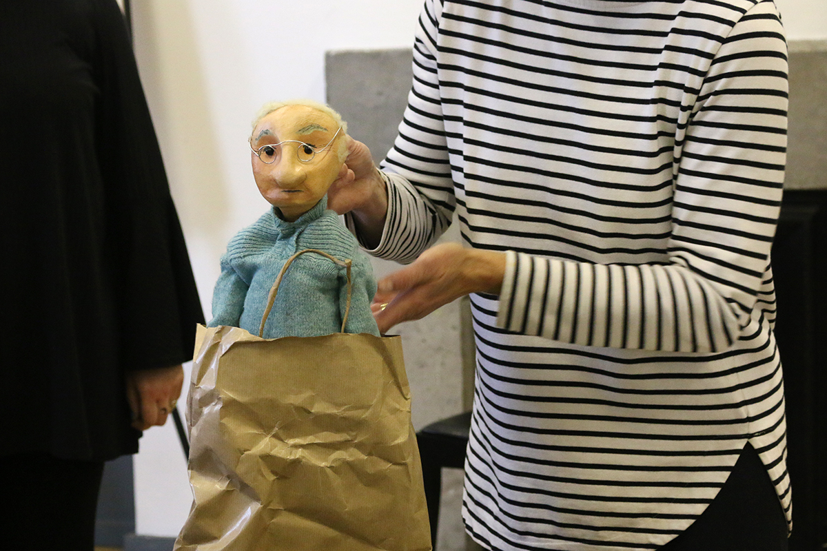 Artist Sarah Fuller animating handmade puppet of old man